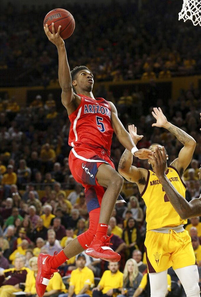 Arizona guard Brandon Randolph (5) drives past Arizona State guard Rob Edwards, right, during the first half of an NCAA college basketball game Thursday, Jan. 31, 2019, in Tempe, Ariz. (AP Photo/Ross D. Franklin)