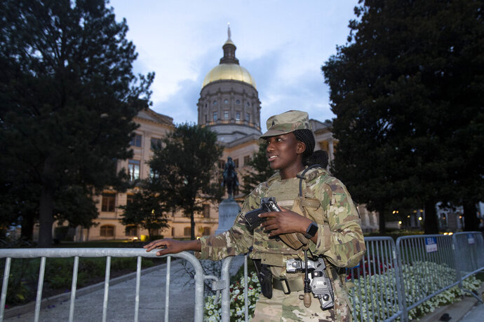 A member of the Georgia National Guard stands outside the State Capitol on Tuesday, July 7, 2020, in Atlanta. Georgia Gov. Brian Kemp mobilized the guard after a surge in gun violence in the city over the weekend. (AP Photo/John Bazemore)