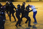 FILE - In this Aug. 10, 2020 file photo, police in Minsk, Belarus, clash with a protester after the Aug. 9 presidential election – a vote that demonstrators denounced as fraudulent. Police used tear gas, flash grenades and beatings in a harsh crackdown. Belarus President Alexander Lukashenko has relied on massive arrests and intimidation tactics to hold on to power despite nearly three months of protests sparked by his re-election to a sixth term, but continuing protests have cast an unprecedented challenge to his 26-year rule. (AP Photo, File)