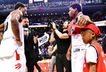 Toronto Raptors guard Kyle Lowry, top right, celebrates with his son Karter and teammate DeMar DeRozan after the Raptors defeated the Washington Wizards 114-106 in Game 1 of an NBA basketball first-round playoff series in Toronto on Saturday, April 14, 2018. (Frank Gunn/The Canadian Press via AP)