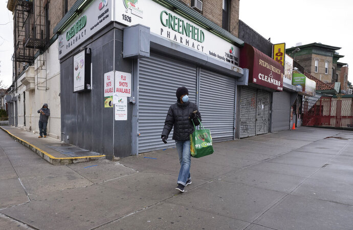 In this Friday, April 3, 2020, photo, a woman walks by local stores during the coronavirus pandemic in New York. Small business owners hoping for quick help from the government's emergency $349 billion lending program were still waiting Tuesday, April 7, 2020, amid reports of computer problems at the Small Business Administration.(AP Photo/Mark Lennihan)
