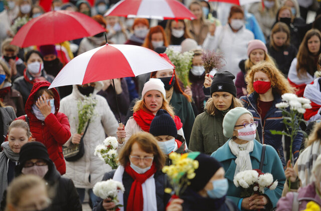 Belarusian women with umbrellas in the colors of the old Belarusian national flag take part in an opposition rally to protest the official presidential election results in Minsk, Belarus, Saturday, Oct. 24, 2020. Several hundred women have marched under heavy rain across the Belarusian capital to demand the resignation of the country's authoritarian president. (AP Photo)