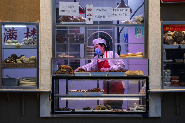 In this photo taken Saturday, Feb. 22, 2020, a chef works near display of food products at a restaurant in Beijing. Small, mostly private companies that are the engine of China's economy are back to operating at one-third of normal levels after anti-virus controls shut factories, shops and restaurants, regulators said Thursday, Feb. 27, 2020 and they promised more low-cost loans and other aid. (AP Photo/Ng Han Guan)