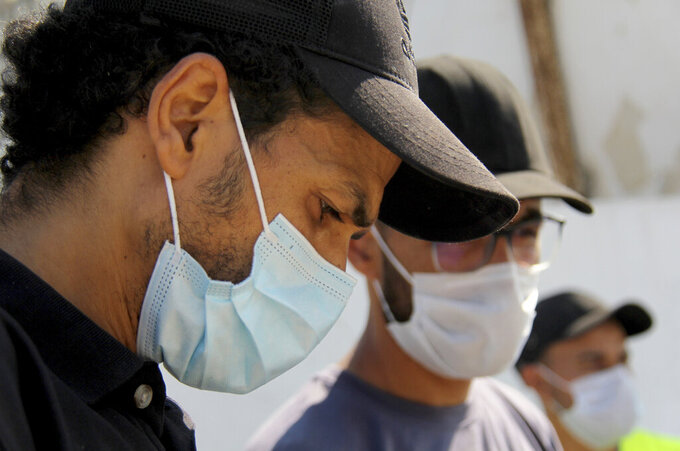 People wearing face masks to protect from COVID-19 stand outside a hospital in Tunis, Tunisia, Wednesday, July 21, 2021. Tunisia's president on Wednesday ordered the military to take over management of the national COVID-19 pandemic response, as the country fights one of Africa's worst outbreaks. (AP Photo/Hassene Dridi)
