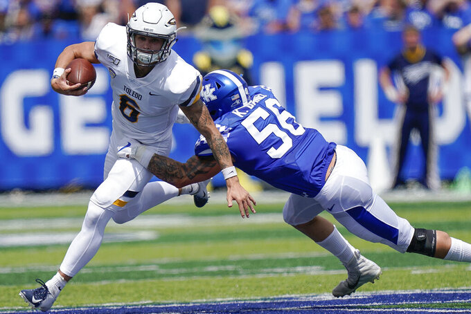 Toledo quarterback Mitchell Guadagni (6) is tackled by Kentucky linebacker Kash Daniel (56) during the first half of the NCAA college football game, Saturday, Aug. 31, 2019, in Lexington, Ky. (AP Photo/Bryan Woolston)
