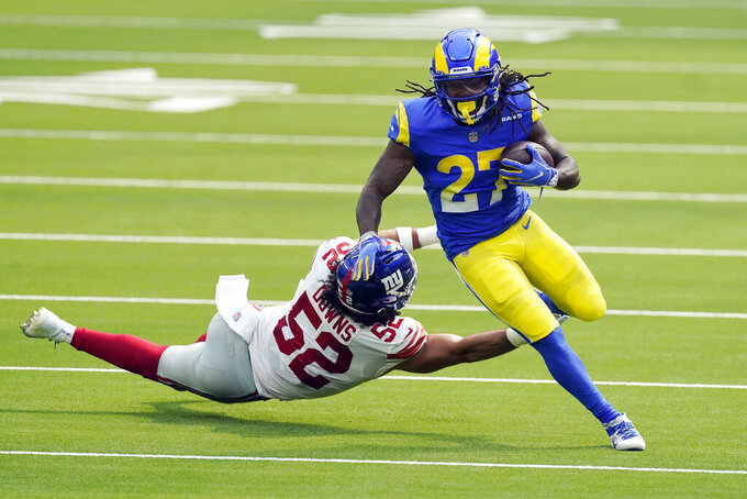 Los Angeles Rams running back Darrell Henderson (27) runs past New York Giants linebacker Devante Downs during the first half of an NFL football game Sunday, Oct. 4, 2020, in Inglewood, Calif. (AP Photo/Ashley Landis)