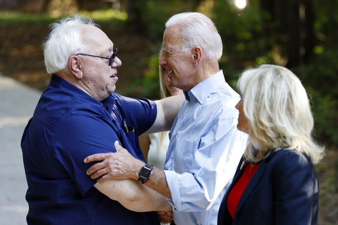 Former Vice President and Democratic presidential candidate Joe Biden greets a local resident as he arrives to speak at a house party at former Agriculture Secretary Tom Vilsack's house, Monday, July 15, 2019, in Waukee, Iowa. (AP Photo/Charlie Neibergall)