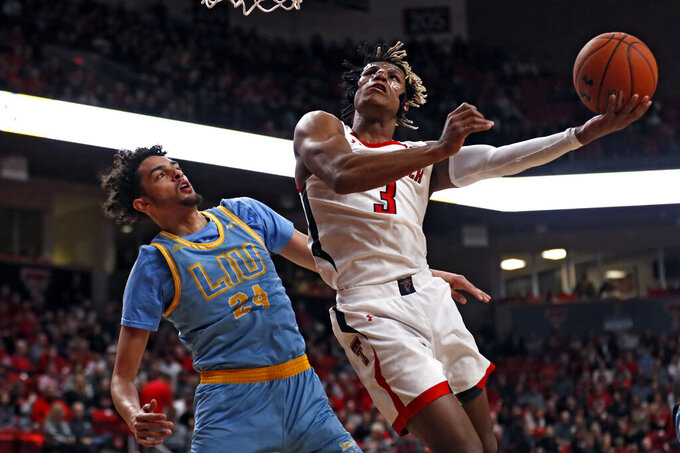 Texas Tech's Jahmi'us Ramsey (3) lays up the ball around Long Island's Ty Flowers (24) during the first half of an NCAA college basketball game Sunday, Nov. 24, 2019, in Lubbock, Texas. (AP Photo/Brad Tollefson)