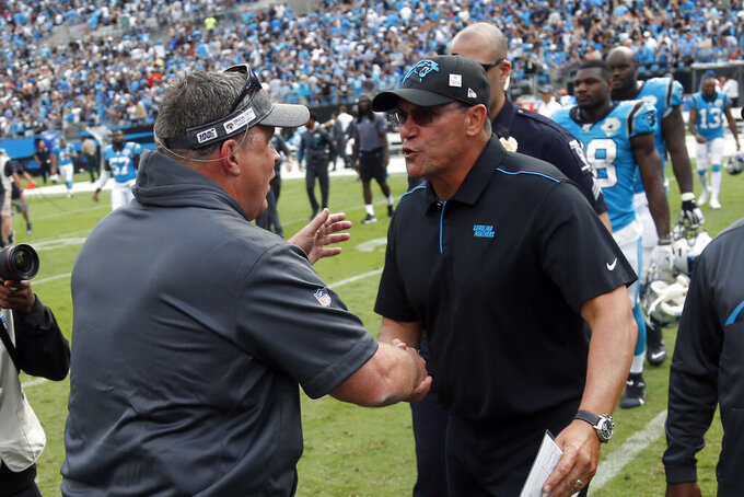 Jacksonville Jaguars head coach Doug Marrone, left, and Carolina Panthers head coach Ron Rivera speak following an NFL football game in Charlotte, N.C., Sunday, Oct. 6, 2019. (AP Photo/Brian Blanco)