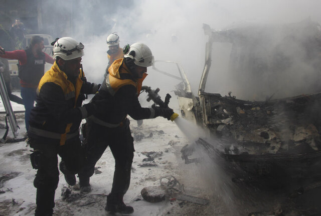 This photo provided by the Syrian Civil Defense White Helmets, which has been authenticated based on its contents and other AP reporting, shows Syrian White Helmet civil defense workers extinguish a burning car that was hit by Syrian government airstrikes, in Idlib province, Syria, Wednesday, Jan. 15, 2020. Syrian government warplanes struck a market and an industrial area on Wednesday in the last territory in the hands of rebel groups in the country's northwest, killing at least 15 people, opposition activists said. (Syrian Civil Defense White Helmets via AP)