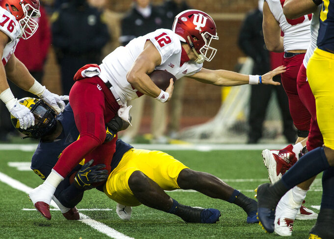 Indiana quarterback Peyton Ramsey (12) tries to escape a tackle from Michigan defensive lineman Kwity Paye, bottom, in the first quarter of an NCAA college football game in Ann Arbor, Mich., Saturday, Nov. 17, 2018. (AP Photo/Tony Ding)