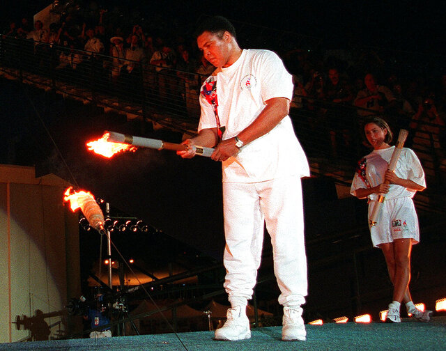 FILE - In this July 19, 1996, file photo, Muhammad Ali, is watched by U.S. swimmer Janet Evans as he lights the Olympic flame during the 1996 Summer Olympic Games opening ceremony in Atlanta. The Olympic cauldron used in the 1996 Games in Atlanta is scheduled to be publicly lit again for the first time in over two decades on Saturday, Feb. 29, 2020. (AP Photo/Michael Probst, File)