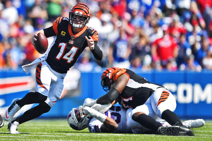 Cincinnati Bengals' Andy Dalton (14) looks to pass as offensive tackle Andre Smith, right, blocks Buffalo Bills' Jerry Hughes during the first half of an NFL football game Sunday, Sept. 22, 2019, in Orchard Park, N.Y. (AP Photo/Adrian Kraus)