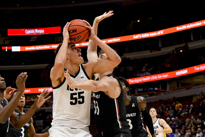 Iowa center Luka Garza (55) shoots against Cincinnati center Chris Vogt (33) during the first half of an NCAA college basketball game Saturday, Dec. 21, 2019, in Chicago. (AP Photo/Matt Marton)
