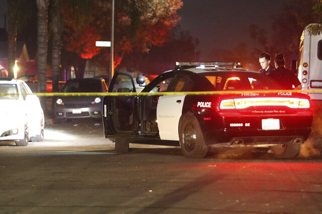 FILE - In this Nov. 17, 2019 file photo police work at the scene of a shooting in southeast Fresno, Calif. Police in California announced Tuesday, Dec. 31, 2019, they have arrested six suspected gang members in the shooting deaths of four men last month at a backyard gathering of family and friends. (Larry Valenzuela/The Fresno Bee via AP,File)