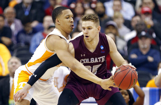 Tennessee's Grant Williams, left, tries to knock the ball loose from Colgate's Rapolas Ivanauskas in the first half of a first-round game in the NCAA men's college basketball tournament in Columbus, Ohio, Friday, March 22, 2019. Tennessee won 77-70. (AP Photo/Paul Vernon)