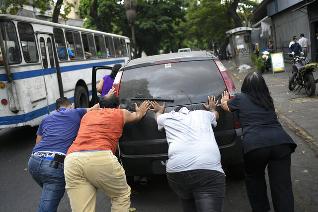 People push a car that ran out of gas to a state-run oil company PDVSA filling station in Caracas, Venezuela, Monday, May 25, 2020. The first of five tankers loaded with gasoline sent from Iran this week is expected to temporarily ease Venezuela's fuel crunch while defying Trump administration sanctions targeting the two U.S. foes. (AP Photo/Matias Delacroix)