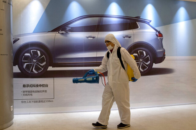 In this Feb. 12, 2020, photo, a worker disinfects a mall near an advertisement for a car in Beijing, China. Automakers are gradually reopening factories in China that were idled by anti-virus control. (AP Photo/Ng Han Guan)