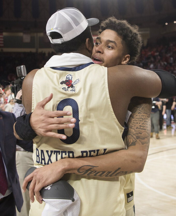 Liberty gard Caleb Homesley, right, hugs Myo Baxter -Bell after defeating Lipscomb in the Atlantic Sun Conference NCAA basketball championship game in Lynchburg, Va., Sunday, March 8, 2020. (AP Photo/Lee Luther Jr.)