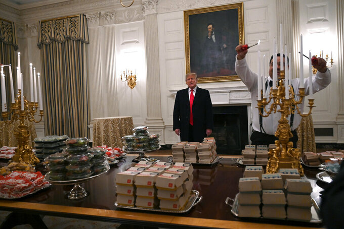 President Donald Trump talks to the press about the table full of fast food in the State Dining Room of the White House in Washington, Monday, Jan. 14, 2019, for the reception for the Clemson Tigers. (AP Photo/Susan Walsh)