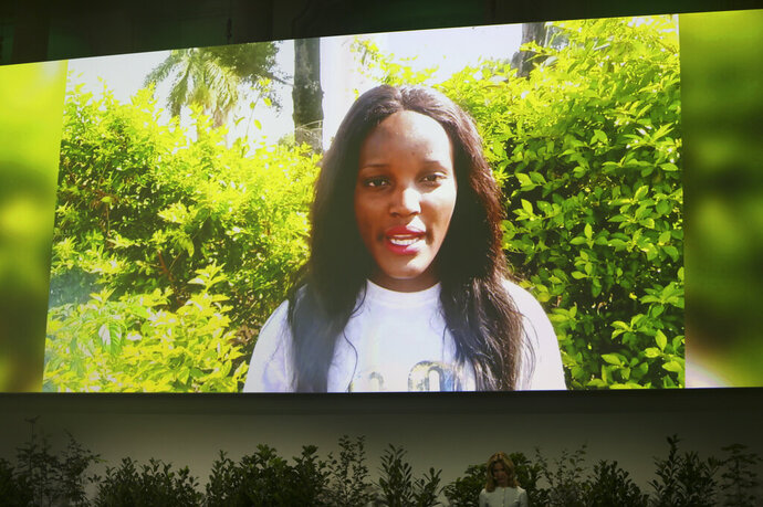 """File - In this Sept. 17, 2020 file photo Ugandan climate activist Vanessa Nakate on a screen as she speaks via video at the 'Austrian World Summit' in Vienna, Austria. Nakate has challenged world leaders to """"wake up"""" and recognize climate change as a crisis. In a speech broadcast on Wednesday, Oct. 7, 2020, as part of the Desmond Tutu International Peace Lecture, she tied the issue to poverty, hunger, disease, conflict and even violence against women and girls. (AP Photo/Ronald Zak, File)"""