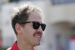 Ferrari driver Sebastian Vettel of Germany smiles as arrives at the track at the Formula One Bahrain International Circuit in Sakhir, Bahrain, Thursday, March 28, 2019. The Bahrain Formula One Grand Prix will take place on Sunday. (AP Photo/Hassan Ammar)