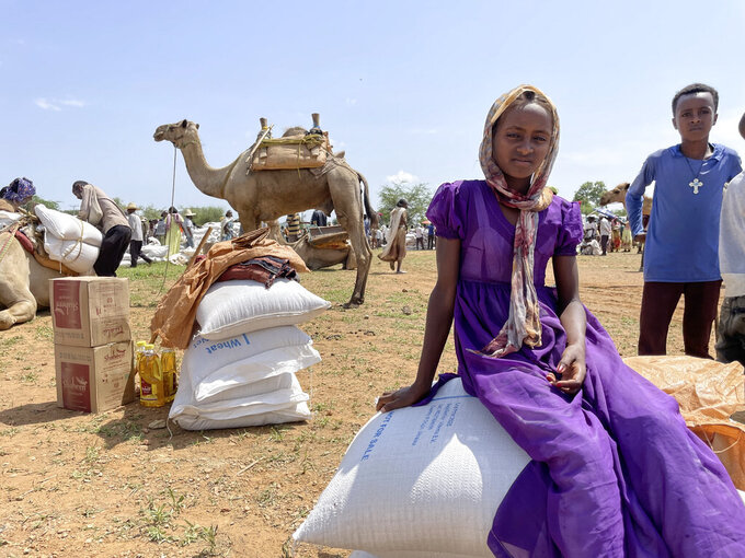 A young Tigrayan girl sits on sacks of wheat after the World Food Programme (WFP) distributed food to around 13,000 people in the rural village of Zelazle in the Tigray region of northern Ethiopia Monday, Aug. 23, 2021. (Claire Nevill/WFP via AP)