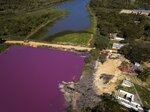 A road divides the Cerro Lagoon, where the water below the road is colored and the Waltrading S.A. tannery stands on the bank, bottom right, in Limpio, Paraguay, Wednesday, Aug. 5, 2020. According to Francisco Ferreira, a technician at the National University Multidisciplinary Lab. who is taking water samples at the site on Wednesday, the color of the water is due to the presence of heavy metals like chromium, commonly used in the tannery process. (AP Photo/Jorge Saenz)
