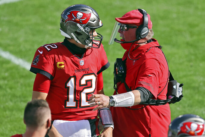 Tampa Bay Buccaneers head coach Bruce Arians congratulates quarterback Tom Brady (12) after a touchdown pass to wide receiver Scott Miller (10) during the first half of an NFL football game against the Minnesota Vikings Sunday, Dec. 13, 2020, in Tampa, Fla. (AP Photo/Mark LoMoglio)