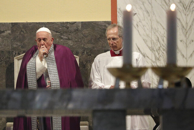 In this picture taken Wednesday, Feb. 26, 2020, Pope Francis coughs inside the Basilica of Saint Anselmo prior to the start of a procession to the Basilica of Santa Sabina before the Ash Wednesday Mass opening Lent, the forty-day period of abstinence and deprivation for Christians before Holy Week and Easter, in Rome. Pope Francis is sick and skipped a planned Mass with Rome clergy across town on Thursday, Feb. 27, 2020, officials said. (AP Photo/Gregorio Borgia)