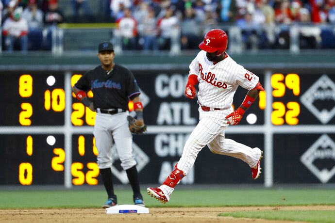 Philadelphia Phillies' Andrew McCutchen, right, rounds the bases past Miami Marlins second baseman Starlin Castro after hitting a home run off starting pitcher Trevor Richards during the fourth inning of a baseball game, Saturday, April 27, 2019, in Philadelphia. (AP Photo/Matt Slocum)
