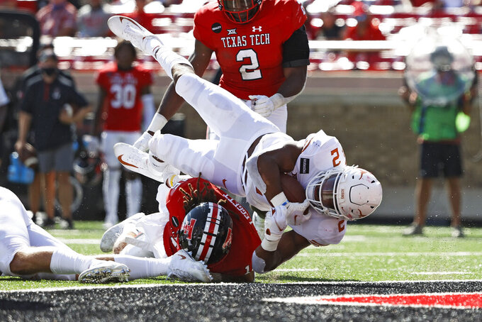 Texas' Roschon Johnson (2) lands in the end zone to score a touchdown during the first half of an NCAA college football game against Texas Tech, Saturday, Sept. 26, 2020, in Lubbock, Texas. (Brad Tollefson/Lubbock Avalanche-Journal via AP)
