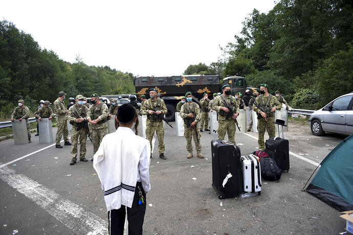 Ukrainian border guards block the road on the Belarus-Ukraine border, in Belarus, Tuesday, Sept. 15, 2020. About 700 Jewish pilgrims are stuck on Belarus' border due to coroavirus restrictions that bar them from entering Ukraine. Thousands of pilgrims visit the city each September for Rosh Hashana, the Jewish new year. However, Ukraine closed its borders in late August amid a surge in COVID-19 infections. (TUT.by via AP)
