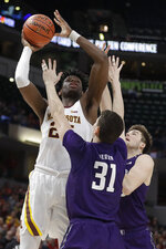 Minnesota's Daniel Oturu (25) puts up a shot over Northwestern's Robbie Beran (31) during the first half of an NCAA college basketball game at the Big Ten Conference tournament, Wednesday, March 11, 2020, in Indianapolis. (AP Photo/Darron Cummings)