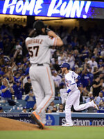 Los Angeles Dodgers' Cody Bellinger, rear, rounds third after hitting a two-run home run off San Francisco Giants relief pitcher Dereck Rodriguez, foreground, during the seventh inning of a baseball game Wednesday, June 19, 2019, in Los Angeles. (AP Photo/Mark J. Terrill)