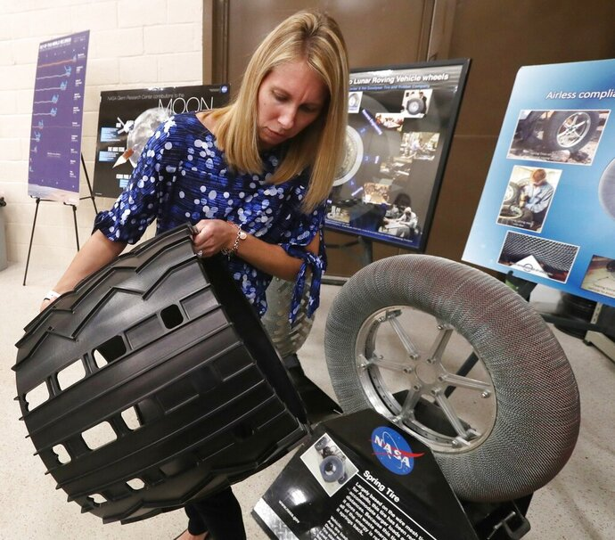 Heather Oravec, research associate professor stationed at the NASA Glenn Research Center, holds a spare aluminum tire for the Mars Curiosity rover in the Simulated Lunar Operations Lab in Cleveland on Sept. ,9, 2019. Oravec's research in extraterrestrial soil mechanics and extraterrestrial surface mobility helps in developing new tires for off world vehicles and rovers. (Mike Cardew/Akron Beacon Journal via AP)