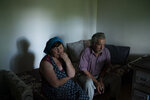 In this June 19, 2019 photo, Jorgji Ilia, 71, a retired schoolteacher, sits with his wife, Vito, 64, inside their home in the village of Kanikol, Albania.