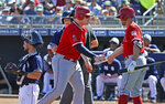 Los Angeles Angels' Justin Bour, middle, celebrates his run scored against the San Diego Padres with Peter Bourjos, right, as Padres catcher Austin Hedges, left, waits at home plate during the first inning of a spring training baseball game Sunday, March 17, 2019, in Peoria, Ariz. (AP Photo/Ross D. Franklin)