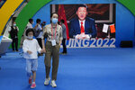 A woman and child wearing masks pass by a screen displaying Chinese President Xi Jinping during the China International Fair for Trade in Services (CIFTIS) in Beijing Sunday, Sept. 5, 2021. An avalanche of changes launched by China's ruling Communist Party has jolted everyone from tech billionaires to school kids. Behind them: Xi's vision of reviving an idealized early era of vigorous party leadership, with more economic equality and tighter control over society and billionaire entrepreneurs. (AP Photo/Ng Han Guan)