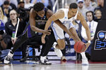 Washington's Noah Dickerson, left, and North Carolina's Garrison Brooks battle for a loose ball in the first half during a second round men's college basketball game in the NCAA Tournament in Columbus, Ohio, Sunday, March 24, 2019. (AP Photo/Tony Dejak)