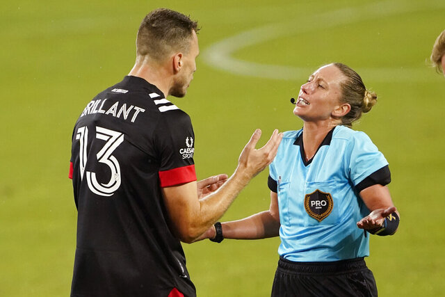 D.C. United defender Frédéric Brillant (13) argues with referee Tori Penso during the first half of the team's MLS soccer match against Nashville SC on Wednesday, Sept. 23, 2020, in Nashville, Tenn. Penso is the first woman to officiate a Major League Soccer match in 20 years. (AP Photo/Mark Humphrey)