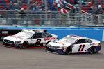 Brad Keselowski (2) and Denny Hamlin (11) race side by side through Turn 4 during the NASCAR Cup Series auto race at Phoenix Raceway, Sunday, Nov. 8, 2020, in Avondale, Ariz. (AP Photo/Ralph Freso)