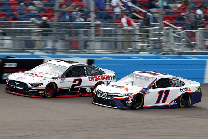 Brad Keselowski (2) and Denny Hamlin (11) race side by side through Turn 4 during the NASCAR Cup Series auto race at Phoenix Raceway, Sunday, Nov. 8, 2020, in Avondale, Ariz. (AP Photo/Ralph Freso)