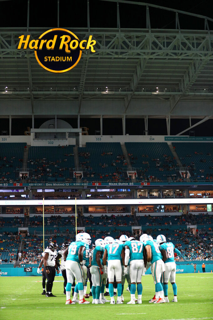 The Miami Dolphins huddle beneath the Hard Rock Stadium sign prior to the snap during an NFL preseason game against the Jacksonville Jaguars, Thursday, Aug. 22, 2019, in Miami Gardens, Fla. (Margaret Bowles via AP)