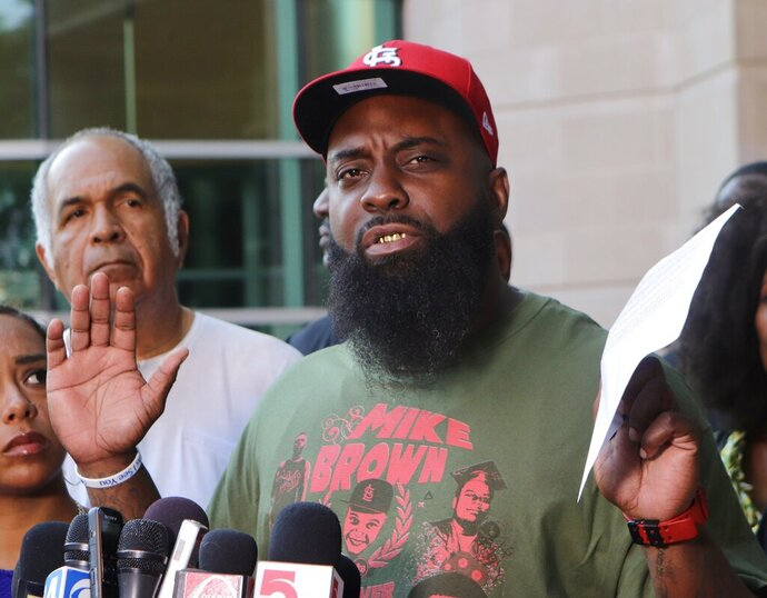 Michael Brown Sr. speaks to the media on Friday, Aug.  9, 2019, the fifth anniversary of the death of his son, Michael Brown, in front of the justice center in Clayton, Mo. Brown asked St. Louis County Prosecutor Wesley Bell to re-examine the evidence in his son's death in hopes of reopening the case. (Hillary Levin/St. Louis Post-Dispatch via AP)