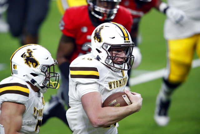 Wyoming quarterback Levi Williams (15) keeps the ball and makes a touchdown run against UNLV during the first half of an NCAA college football game in Las Vegas on Friday, Nov. 27, 2020. (Steve Marcus/Las Vegas Sun via AP)
