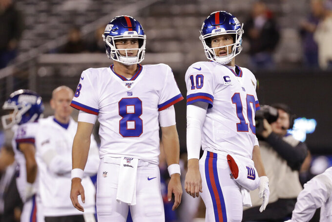 "FILE - In this Nov. 4, 2019, file photo, New York Giants quarterback Daniel Jones (8) and quarterback Eli Manning (10) warm up before an NFL football game against the Dallas Cowboys, in East Rutherford, N.J. Giants quarterback Daniel Jones was kept out of practice Wednesday, Dec. 4, 2019, with a high right ankle sprain, and coach Pat Shurmur says Eli Manning ""very likely"" will start Monday night against the Philadelphia Eagles. Shurmur adds that Manning could very well be the starter for the rest of the season. (AP Photo/Adam Hunger, File)"