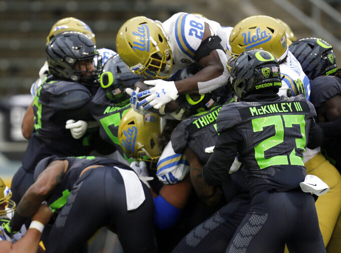 UCLA's Brittain Brown, center, leaps into the end zone for a third-quarter score against Oregon in an NCAA college football game Saturday, Nov. 21, 2020, in Eugene, Ore. (AP Photo/Chris Pietsch)