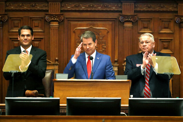 Gov. Brian Kemp, center, is flanked by House Speaker David Ralston, R-Blue Ridge, right, and Lt. Gov. Geoff Duncan as he salutes former U.S. Senator Johnny Isakson, R-Ga., during the State of the State address before a joint session of the Georgia General Assembly Thursday, Jan. 16, 2020, in Atlanta.(AP Photo/John Bazemore)