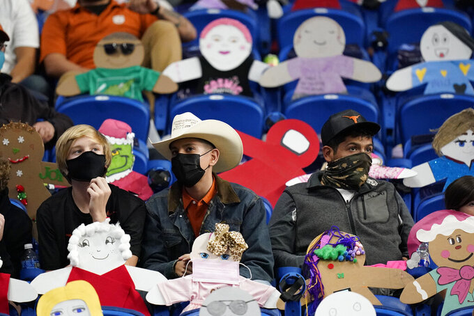 Fans wear face masks as they sit near cutouts of fans during the first half of the Alamo Bowl NCAA college football game between Texas and Colorado, Tuesday, Dec. 29, 2020, in San Antonio. (AP Photo/Eric Gay)